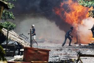 Rohingya men are seen among houses set on fire during fighting between Buddhist Rakhine and Muslim Rohingya communities in Sittwe